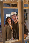 Picture of a man and a woman at a home under construciton and being viewed between two by fours in the unfinished home.